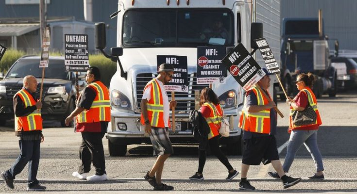 Truck drivers and warehouse workers protest their classification as independent contractors by Los Angeles and Long Beach port trucking companies in October. (Al Seib / Los Angeles Times)